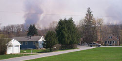 Houses with forest and smoke behind them