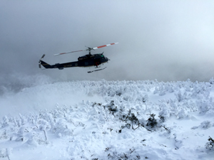 A helicopter flying over the snowy peak of the Adirondack Mountains