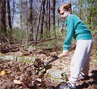 photo of boy turning a compost pile