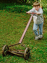 a child using a push mower