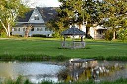 A view of a house, lawn with gazebo and pond in the foreground