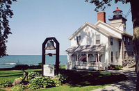 Lighthouse at Sodus Point with house, lawn and lake