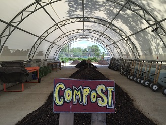 Compost sign in front of long pile of finished compost