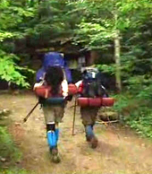 Two hikers with full packs head through the forest on a trail