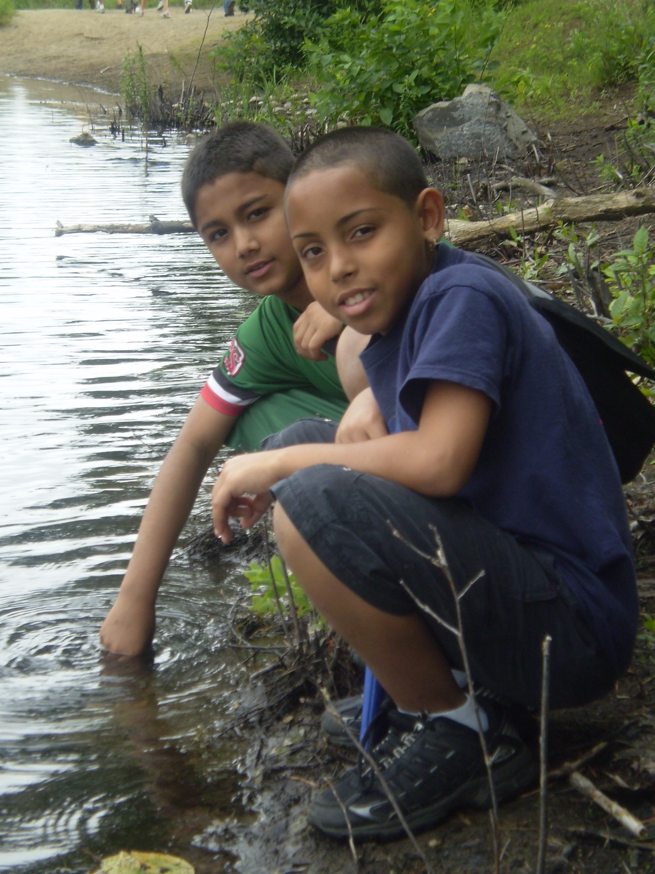 Two young boys kneeling by a body of murky water