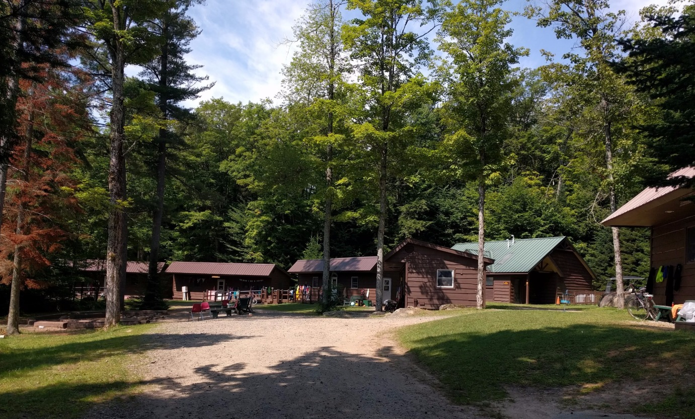 Camper cabins at Camp Colby sit among many trees