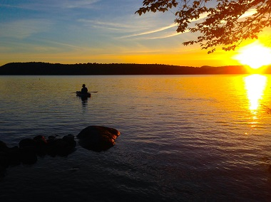 sunset behind a kayaker