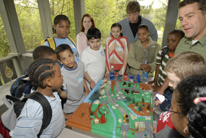 Kids garthered around a table learning about Environmental Education