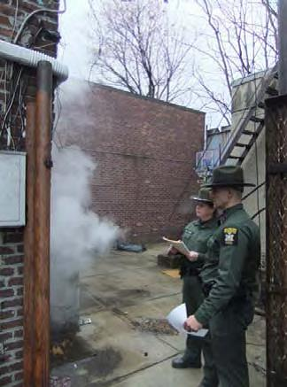 two officers looking at an outdoor furnace spewing out smoke