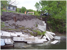 A failed concrete retaining wall lies in pieces at the base of a streambank