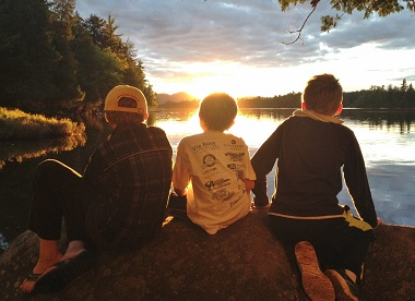 three boys watching the sunset from a rock