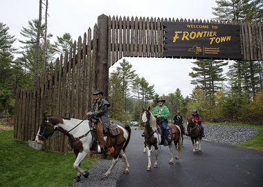 equestrian riders under the frontier town sign