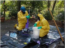Two workers in protective suits and gloves handling hazardous material in a bucket