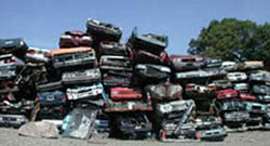 A photo of vehicles stacked at a junk yard.