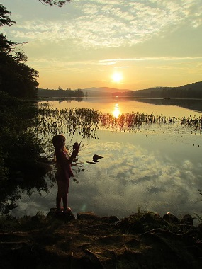 little girl fishing at sunset