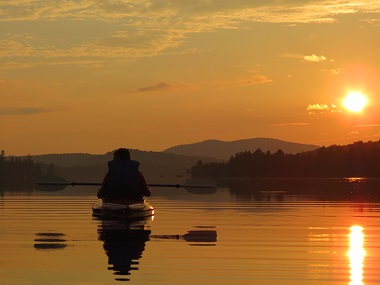 kayaker on the water at sunset