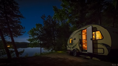a small trailer lit up at night next to the water