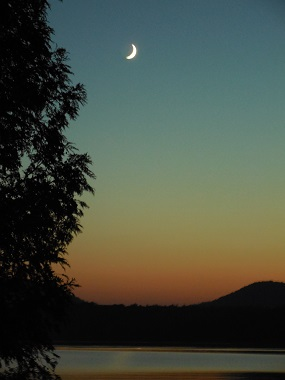 sunset behind the mountains with the moon in the sky