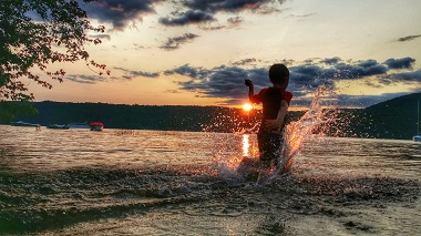 child splashing in the water at sunset
