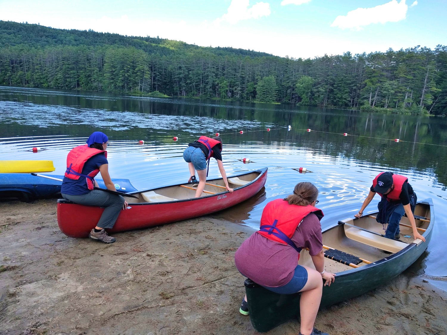 Four campers practice getting in and out of canoes on the lake at Pack Forest
