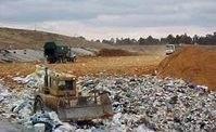 A bulldozer in a pile of garbage at a landfill