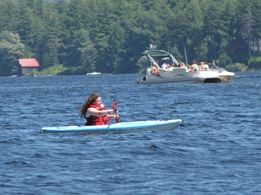 girl kayaking with a motor boat in the background