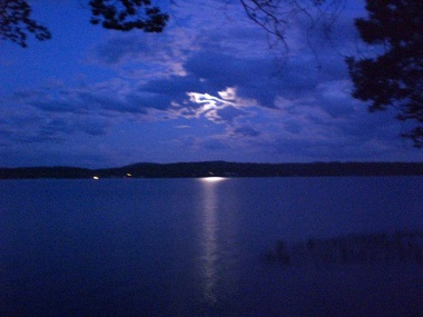 moon behind the clouds over the water