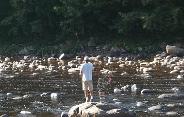 family fishing from rocks on the river