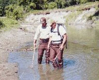 Fisheries staff wading through stream using an back electroshocker to locate larval lamrpey
