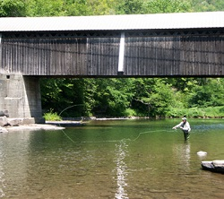 A person in waders fly fishes from the creek by a covered bridge