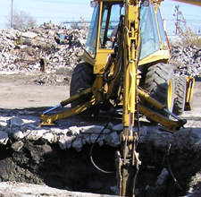 An excavator removes soil at the Frontier Chemical site