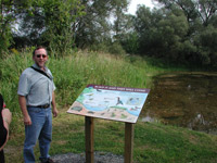Picture of sign and the artist along nature trail