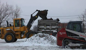 A wheel loader moves contaminated soil for disposal at a permitted facility