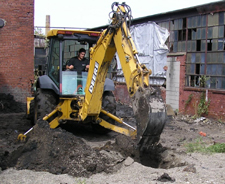 An excavator digs a test pit near the former loading dock area at the Polymer Applications site