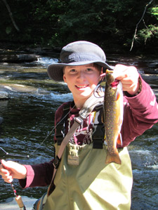 A boy holding up a brook trout caught on the Tug Hill Plateau