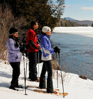 three cross-country skiers standing by a river