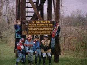 Group photo of people around the Utica Marsh WMA sign
