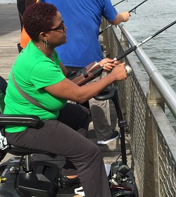 A woman in a wheel chair fishing with others fishing in the background