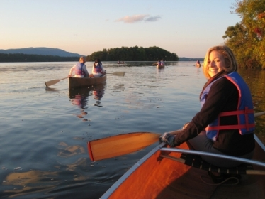 Several canoes with paddlers on the Hudson River at dusk