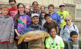 Norrie Point educator in center holding large common carp surrounded by about ten students