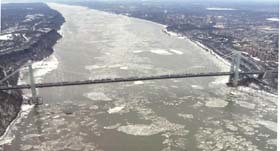 aerial photo of looking north at the George Washington Bridge and the Hudson River wih a lot of ice on it