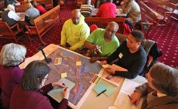 a group of citizens around a table at a town meeting with papers and maps in hand