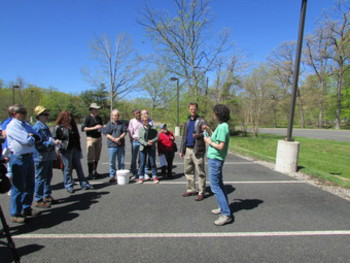 group of adults in a parking lot, watching a speaker/demonstration on a sunny day