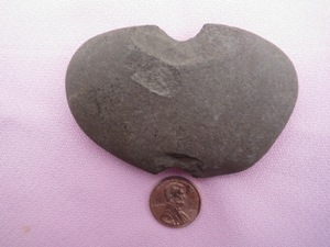 A prehistoric net sinker lays flat next to a penny for size comparison.