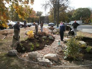 People working on a rain garden with shrubs, perennials, large stones and rocks
