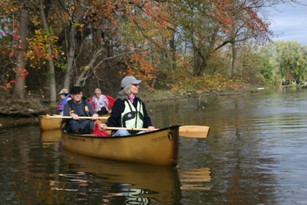Four boaters in two canoes on the river near shore where trees are showing their autumn leaves