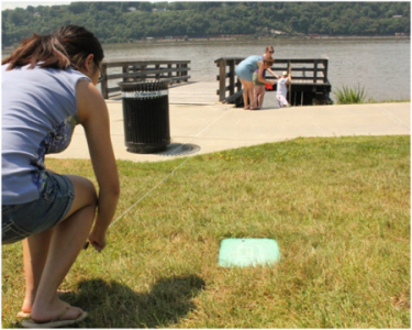 A student stands near the river while measuring the effects of sea level rise.