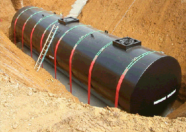 A huge black storage tank being installed underground