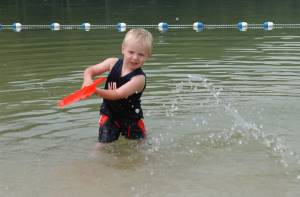Boy playing in water at a regulated swimming beach.