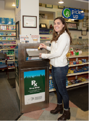 a person drops unwanted medications in a drug takeback box at her local pharmacy